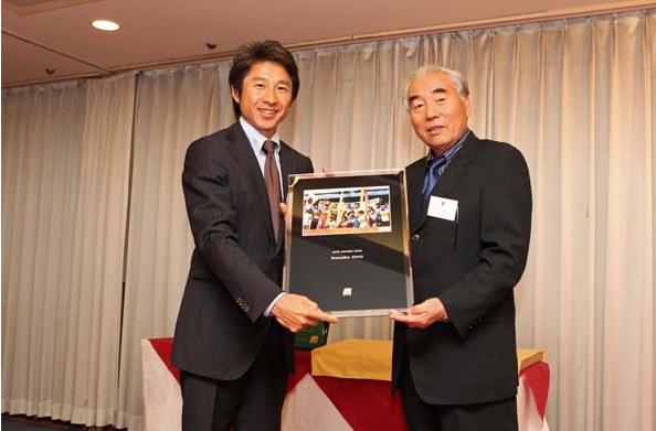 当協会会長水谷章人より故小野学氏に代わり荻原健司氏に記念の写真盾を贈呈